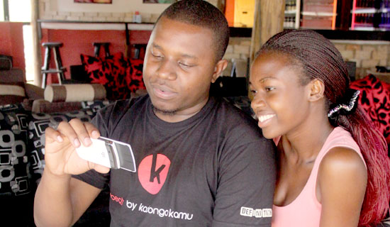 cap: Just Jose shows Val Keko's latest video on his phone. PHOTO BY JONAH KABUGO