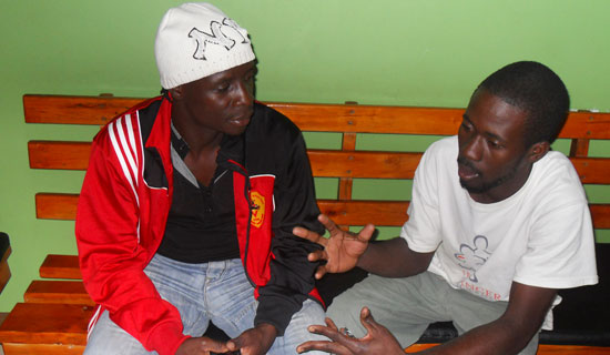 Football striker Robert Ssentongo and his fan Jacob discuss football. PHOTO BY ISAAC SSEJJOMBWE