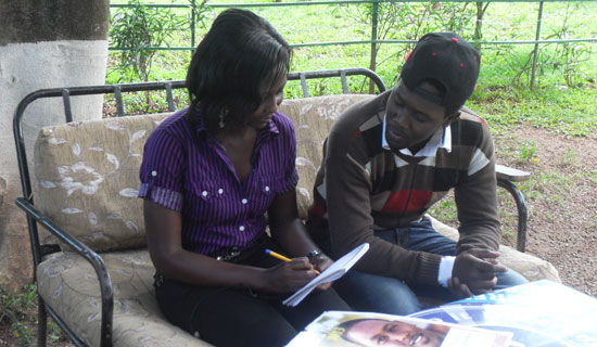 Niki Nola and his fan Betty Nazziwa discuss his music career. PHOTO BY ISAAC SSEJJOMBWE