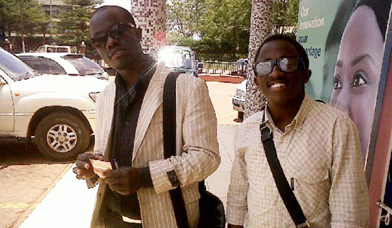 Cricket star Kyobe (right) with fan, Mugabi. PHOTO BY ISAAC SSEJJOMBWE