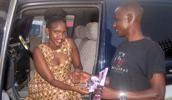 Fille gives Kaziro her music CD. PHOTO BY ISAAC SSEJJOMBWE