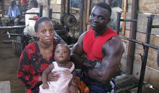 Cobra i s back on his feet after the 2010 shooting. He poses with his wife and child in his gym.  PHOTO BY JUDE KATENDE