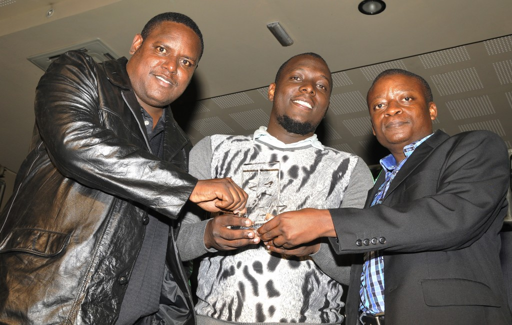 Dembe Fm Presenter Isaac Katende a.k.a Kasuku (C) together with colleagues Jenkens Mukasa (L) and Eddy Ssendi pose with the award that their talk and talk show won