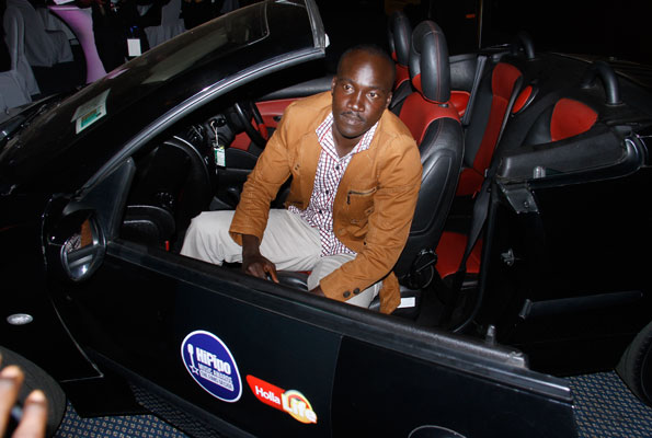 Mr Igama Benedict with swag in his new wheels. Photo by Lubowa Abubaker
