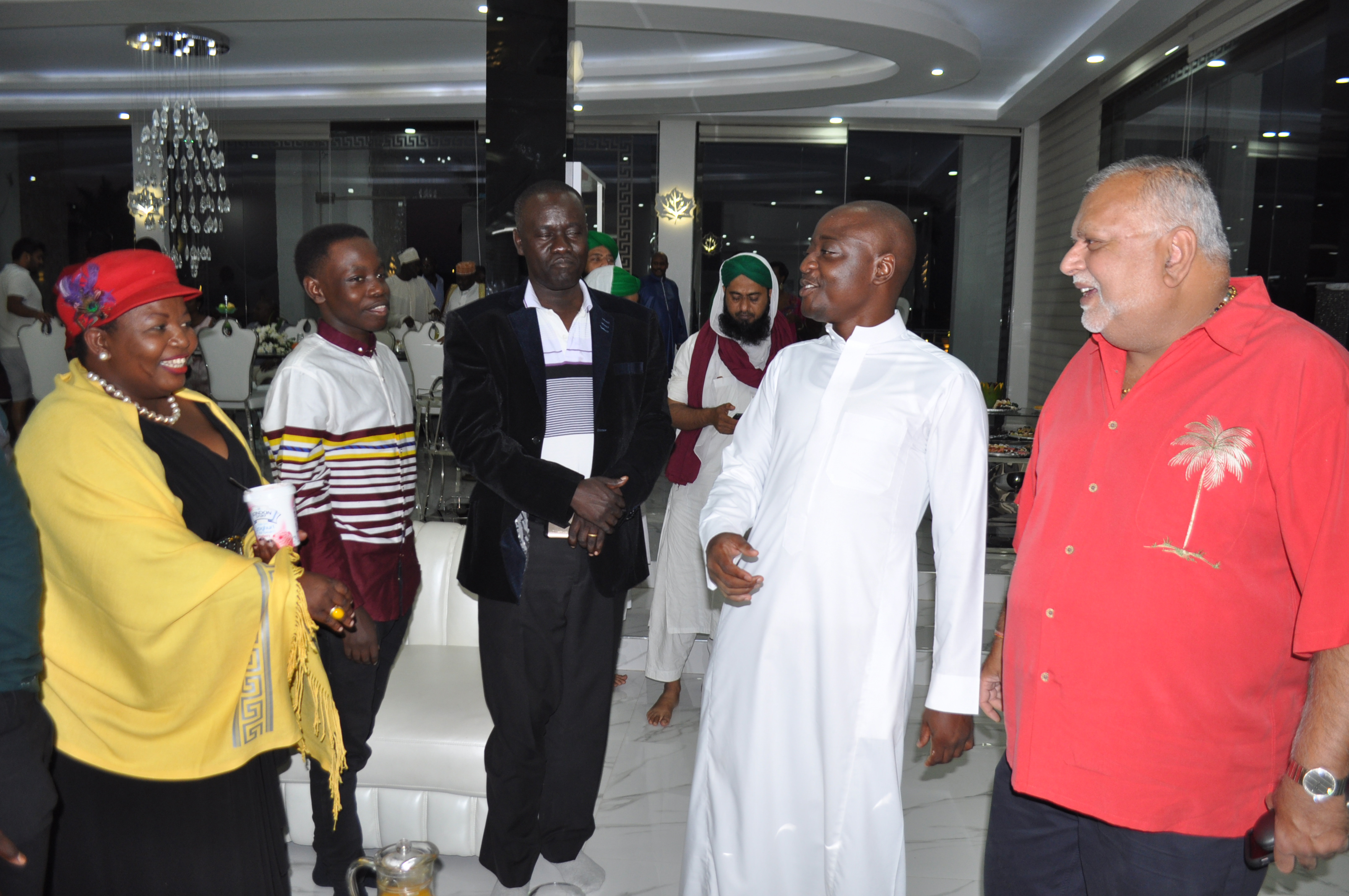 Hamis Kiggundu (in kanzu), chats with NRM Secretary General Justine Lumumba (left) and city tycoon Sudhir Ruparelia (right), who were some of the guests.