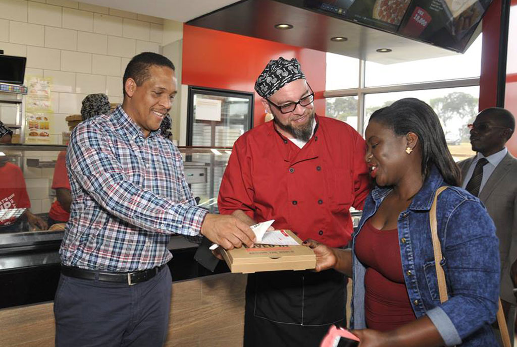 Hans Paulsen (right) hands a pizza to an invited guest at the launch of Pizza Hut in Entebbe. PHOTO BY lawrence ogwal