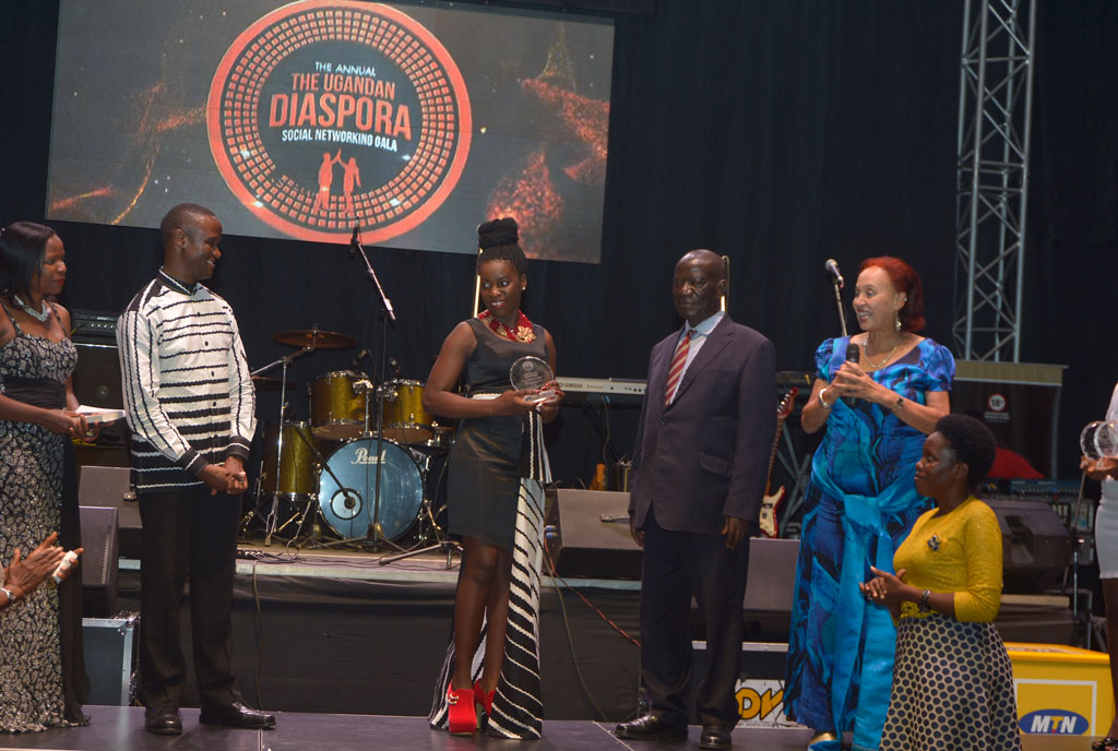 Vice President Edward Kiwanuka Ssekandi (Suit) hands over the Uganda Diaspora Life time Achievement Award to King and Queen of Katwe actress Ms. Phiona Mutesi and coach Robert Katende flanked by his wife  in recognition for their role in marketing Uganda abroad through their film during the 6th Diaspora Gala and social networking dinner at Serena Kampala hotel.