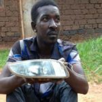 Qute Kaye holding teh headlight he allegedly stole from a car in Busega on Thursday