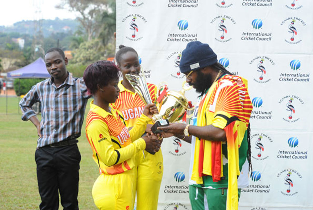 Jamaican Reggae star Riley (R) admires trophies presented to her by the Lady Cricket Cranes skipper Kevin Awino (L) and Janet Mbabazi (C) at the end of the Tarrus Riley Cricket Carnival in Lugogo yesterday